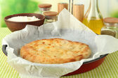 Pita bread in oven-tray with spices on tablecloth on bright background — Stock Photo
