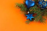 Beautiful Christmas decorations on fir tree on orange background — Stock Photo