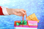 Hand holds package with New Year gifts on blue background — Stock fotografie