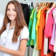 Beautiful young stylist near rack with hangers — Foto de Stock