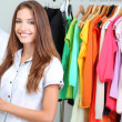 Beautiful young stylist near rack with hangers — Stok fotoğraf