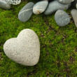 Stock Photo: Grey stone in shape of heart, on grass background