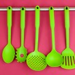Stock Photo: Plastic kitchen utensils on silver hooks on red background