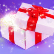 Gift box with bright light on it on purple background — Stock Photo