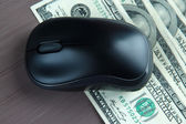 Computer mouse on dollars on wooden background — Stock Photo