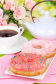Sweet donuts with cup of tea on table on bright background — Stock Photo