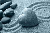 Grey zen stone in shape of heart, on sand background — Zdjęcie stockowe