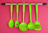 Plastic kitchen utensils on silver hooks on red background — Stock Photo