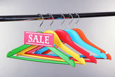 Wooden clothes hangers as sale symbol on gray background — Stock Photo