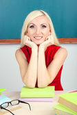 School teacher sitting at table on blackboard background — Stock Photo