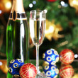 Bottle of champagne with glass and Christmas balls on Christmas tree background — Stock Photo #35201397