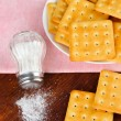 Delicious crackers with salt and napkin on wooden background — Stock Photo