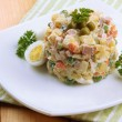 Russian traditional salad Olivier, on color napkin, on wooden background — Stock Photo