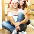 Young couple with boxes in new home celebrating New Years — Stock Photo #35202983