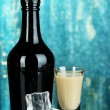 Baileys liqueur in bottle and glass on blue background — Stock Photo