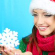 Beautiful smiling girl with Christmas snowflake on blue background — Stock Photo #35205033