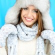 Beautiful smiling girl in hat and mittens on blue background — Stock Photo #35205831
