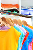 Variety of casual t-shirts on wooden hangers on shelves background — Stok fotoğraf