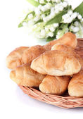 Tasty croissants on wicker mat isolated on white — Stock Photo