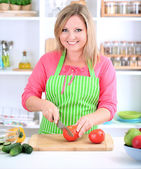 Happy smiling woman in kitchen holding fresh vegetables in her hands — Stock Photo