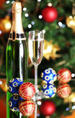 Bottle of champagne with glass and Christmas balls on Christmas tree background — Foto de Stock