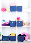 Blue textile boxes with towels and clothes in white shelves — Stock Photo