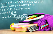 Purple backpack with school supplies on wooden table on green desk background — Stock Photo