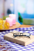 Composition with old book, eye glasses, candles and plaid on bright background — Stock Photo
