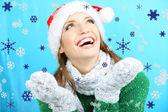 красивая улыбающаяся девочка со снегом на синем фоне — Стоковое фото