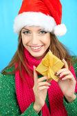 Belle jeune fille souriante au chapeau du nouvel an avec cadeau sur fond bleu — Photo