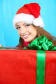 Beautiful smiling girl in New Year hat with gift on blue background — Stock Photo