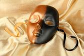 Mask on gold fabric background — Stock Photo