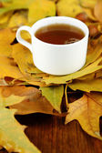 Cup of hot beverage, on yellow leaves, on wooden background — Stock Photo