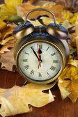 Old clock on autumn leaves on wooden table close-up — Stockfoto