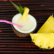 Pina colada drink in coconut, on bamboo mat background — Stock Photo