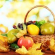 Different fruits and vegetables with yellow leaves in basket on table on bright background — Stock Photo
