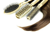 Shiny brown hair with combs isolated on white — Stock Photo