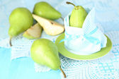 Pear in napkin on plate on wooden table close-up — Stock Photo