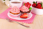Beautiful strawberry cupcakes and flavored tea on dining table close-up — Stock Photo