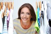 Vacker ung kvinna nära rack med hängare — Stockfoto