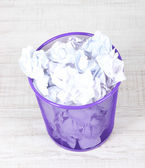 Recycle bin filled with crumpled papers, on floor — Stock Photo