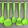 Plastic kitchen utensils on silver hooks on grey background — Stock Photo #35290037