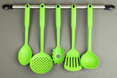 Plastic kitchen utensils on silver hooks on grey background — Stock Photo