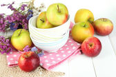 Juicy apples on plate on white wooden table — ストック写真