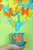 Paper butterflies fly out of pitcher on green wall background — Stock Photo