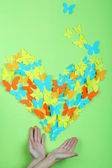 Paper butterflies on hands on green wall background — Stock Photo