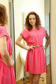 Beautiful girl trying dress near mirror in room — Foto de Stock