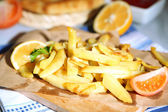 Ruddy fried potatoes on wooden board on table close-up — Stock Photo