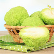 Osage Orange fruits (Maclurpomifera) in basket, on wooden table — Stock Photo #35312587