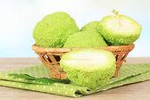 Osage Orange fruits (Maclura pomifera) in basket, on wooden table — Stock Photo
